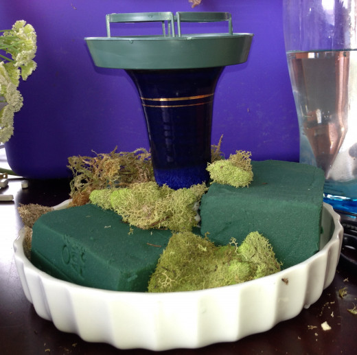 Floral foam in the process of being covered with moss.