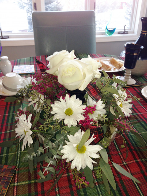 The final arrangement on the dinner table. The table was dressed with a tartan table cover and full length white tablecloth.