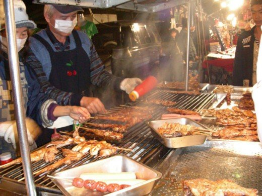 A mobile vendor seasons his Japanese BBQ in Taiwan