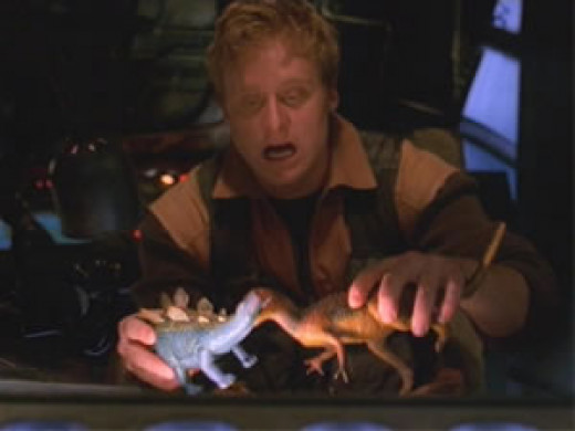 Wash, the ship's pilot playing with his dinosaurs while the others are on a salvage mission.