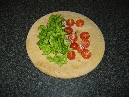 Lettuce is shredded and cherry tomatoes are halved