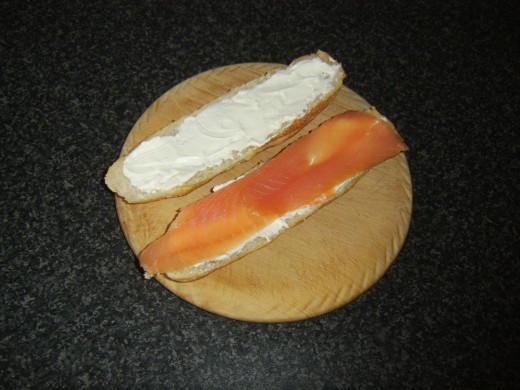 Smoked salmon is laid on bottom half of sub roll