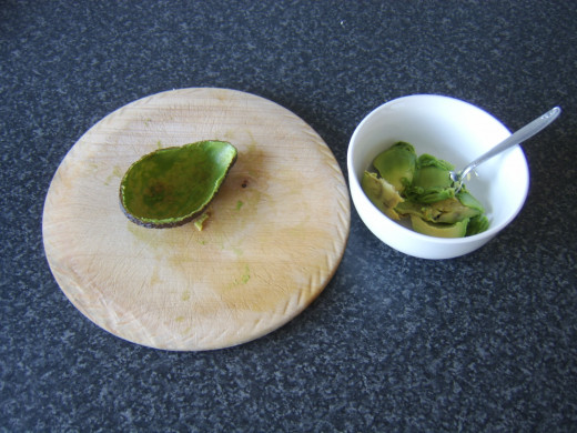 Flesh is scooped out of avocado half with a teaspoon
