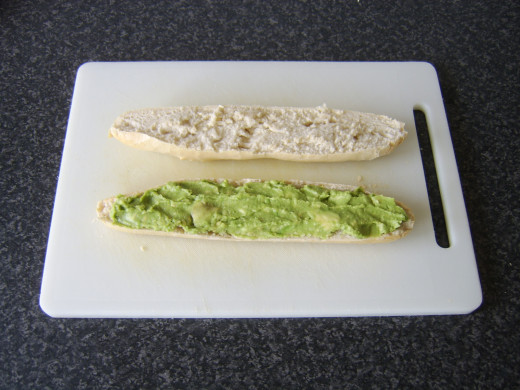Mashed avocado is spread on the bottom half of the baguette