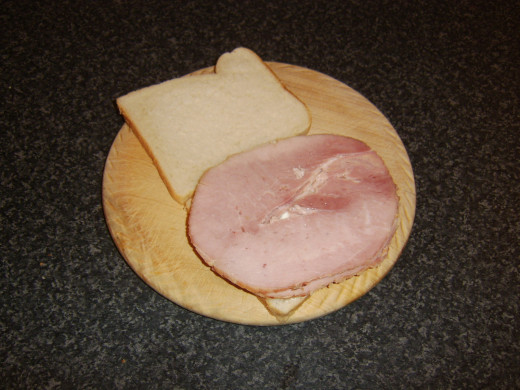 Two thick slices of honey roast ham are laid on cottage cheese