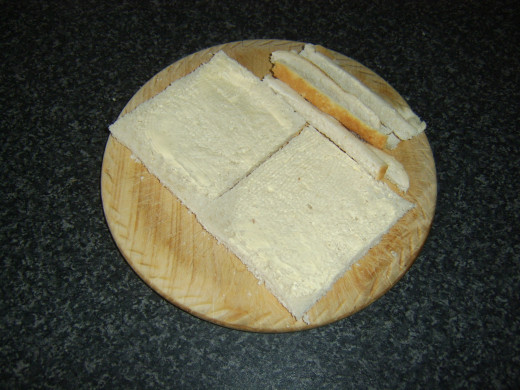 Crusts are cut from lightly buttered bread