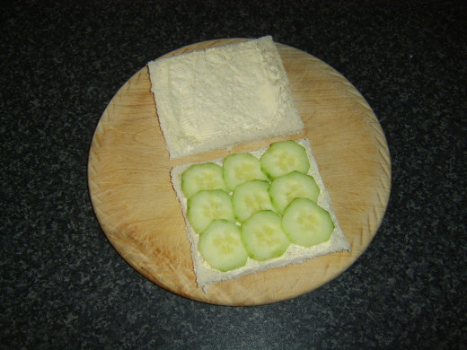 Cucumber slices are laid on one slice of the buttered bread