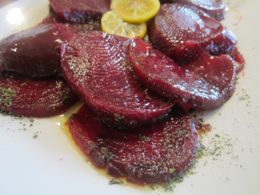 Trim away the roots, cut into slices. Arrange the sliced beets on a serving platter. Drizzle with dressing and mint.