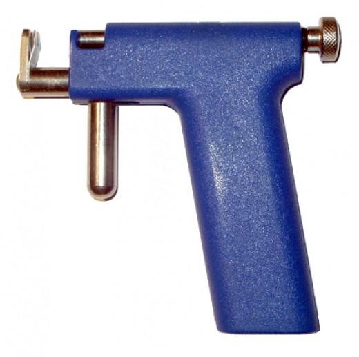 An ear piercing gun is used to pierce ears