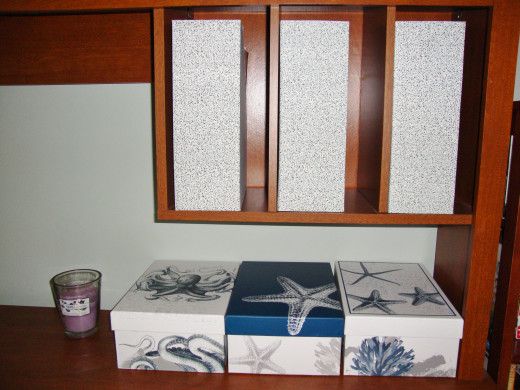 Blue and white, beach themed storage boxes not only hide clutter, but make the space look organized and appealing.
