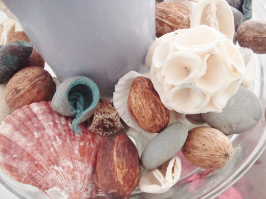 A colorful potpourri mix of shells, stones, dried flowers, and seed pods give a lavendar candle a beachy look.