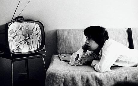 Jagger watching, reportedly, the Red Skelton Show on a small b&w TV