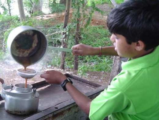 An Indian boy making masala chai (Chai Latte) .