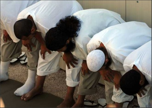 """Detainees bow before they pray in this U.S. Navy handout photo taken at Camp 4, the U.S. Navy Base, Guantanamo Bay, Cuba on Jan. 24, 2008. PETTY OFFICER 3rd CLASS JOSHUA BRUS / US NAVY"""
