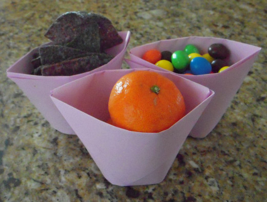 Paper cups can hold many things, like blue corn tortilla chips, M&Ms and even very small mandarin oranges. They can hold water, too.