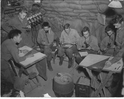 Artillery FDC in Italy. In the back left, you can see the wood rack holding the ubiquitous phones. Also note the use of a sheaf on the plotting tables. This aided in delineating planes of fire for multiple artillery pieces.