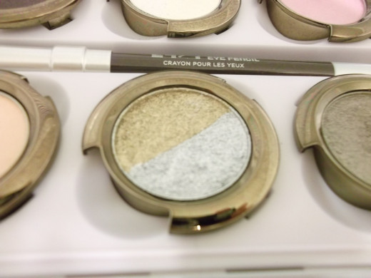 Closeup of Oz eye shadow. There are two separate shadows in this pan. One is glittery gold and the other is glittery grey.
