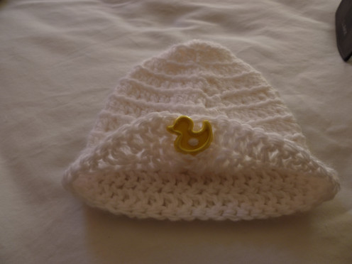 Simple white beanie with a duck button sewn on with bottom edge buttoned up.