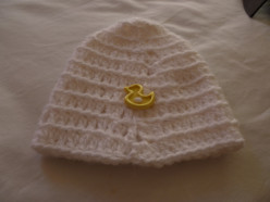 White beanie cap with duck button sewn along bottom half. You can sew on where ever you like