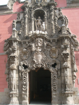 A very ornate  door to the Museo Municipal which is a pink building.