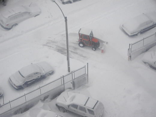 The little plow is at work, clearing snow from the parking lot below me