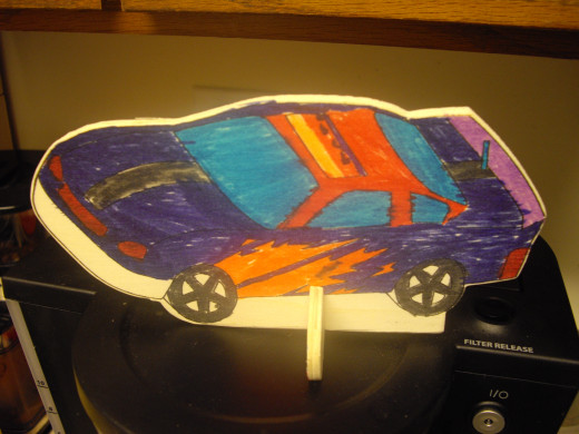 Coloring and playing with cars are two really cool things to do, as a kid. My nephew colored this one