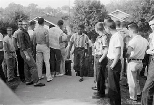 A black student walks through a sea of white students in Clinton, Tennessee.
