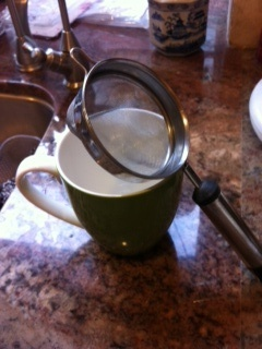Strainer over the cup to strain off the loose tea leaves and ginger