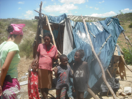 "This family we met were actually land squatters with a makeshift ""house"" of blue tarp and branches.  The mother had four children and one on the way."