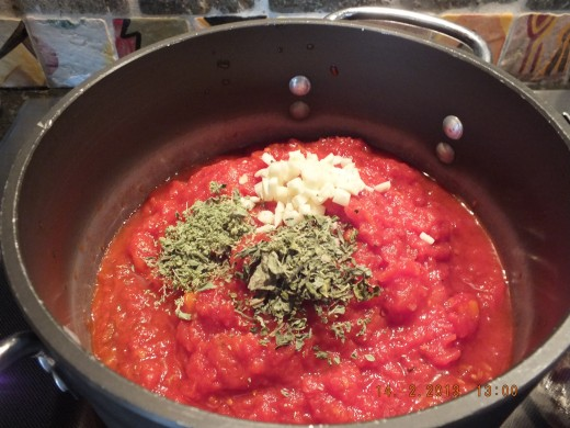 Drop your store-bought sauce into a saucepan and add the dried herbs and garlic.
