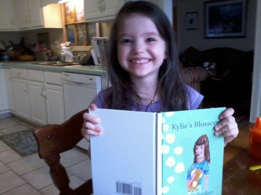 "My granddaughter, Scarlett, reading Maria's book, ""Kylie's Blossoms.""  She loves it!"