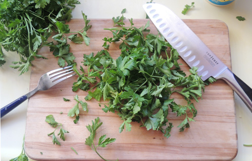 TIP: If you run fork tines through your parsley bunch, gripping bunch firmly by stems, the tines will pull the leaves away from stems, for easy chopping later!