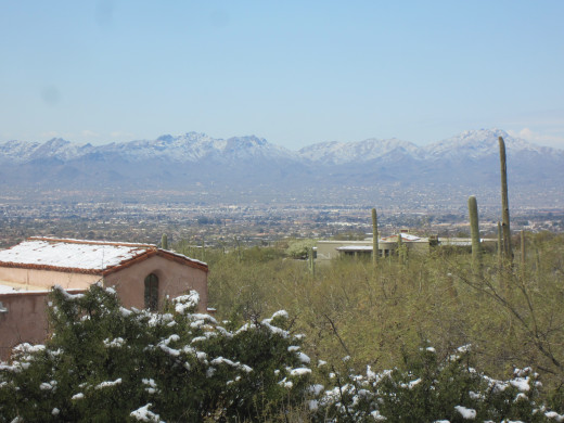 Home next to Finger Rock Trail with the city and snow coveredTucson Mountain Range in background.