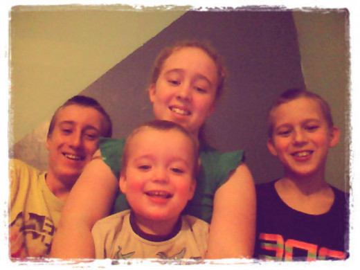 Daddy's girl with her 3 brothers smiling for the camera.