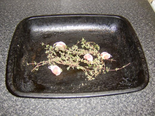Garlic and thyme form bed for roasting chicken