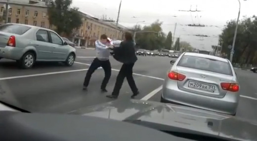 Two men get into a fist fight at a set of traffic lights in Moscow, holding up the other cars on the road