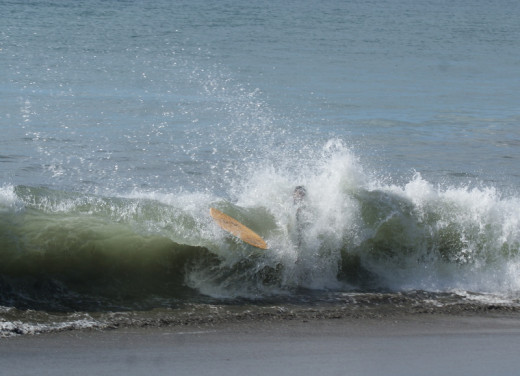 Skim boarding in the surf breaking on the beach on Playa Hermosa one day where there were strong waves.