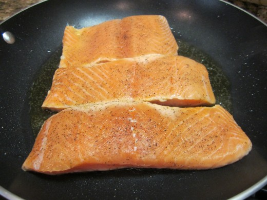 Heat olive oil in a large nonstick skillet over medium heat. Place the salmons in the skillet. Cook for 4 minutes or until golden brown.