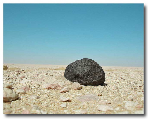 a blackened meteorite stands out on a pale desert landscape