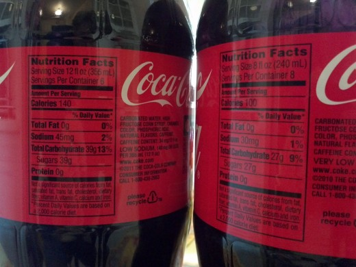 Two versions of a Coca-Cola label - notice the different serving size changes the nutritional data, not the ingredients.