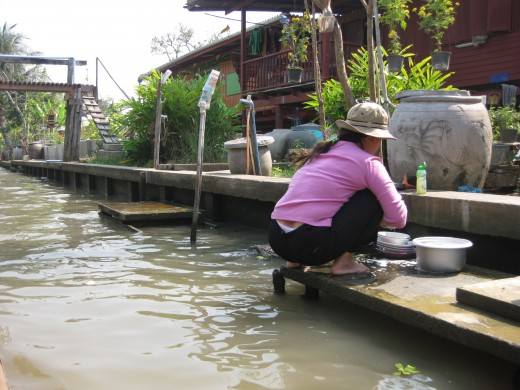 A Thai woman was seen washing the household utensils.