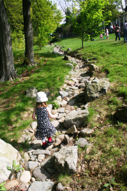 Our daughter walking down a stone path in the middle of an arboretum