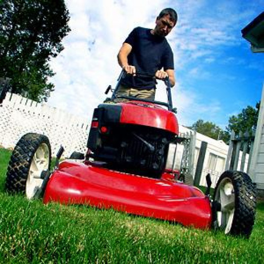 A happy college entrepreneur mowing the lawn!