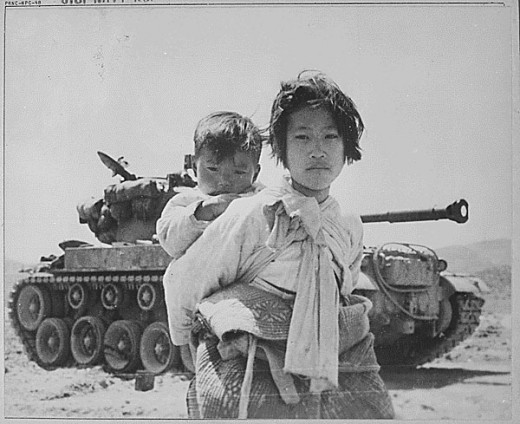 A Korean girl carries her brother past a stalled U.S. tank near Haengju, Korea, June 1951