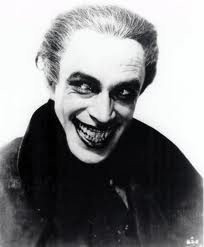 Conrad Veidt in The Man Who Laughs looking very similar to the familiar appearance of the Joker.