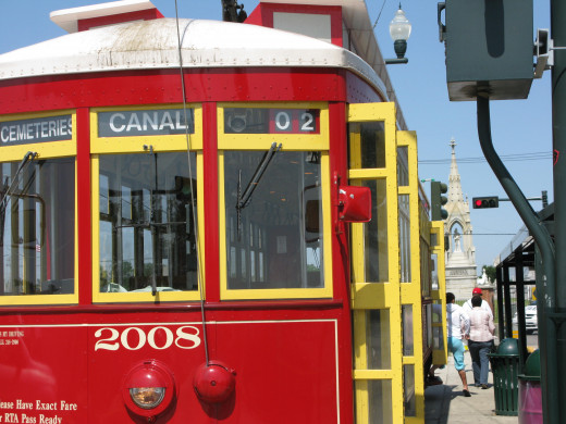 "These distinctive red streetcars will take you ""to the end of the line!"" The spires of Greenwood Cemetery are visible behind."