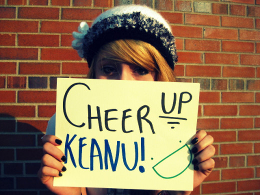 "A Young Woman Offering Keanu Reeves Her Support On ""Cheer Up Keanu Day"""