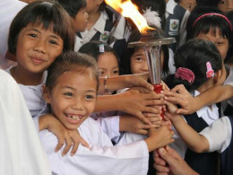 children smiling with the Peace Torch