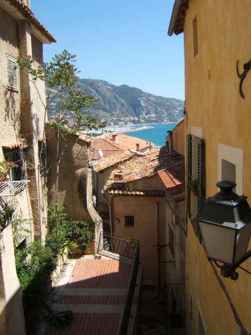 A magnificent view from a pictruesque alley of Old Menton. In the background, the Port of Menton-Garavan may be seen, with the Italian border beyond, to the right.