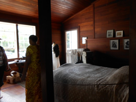 Bedroom in Vailima with a tour guide in native Samoan dress.